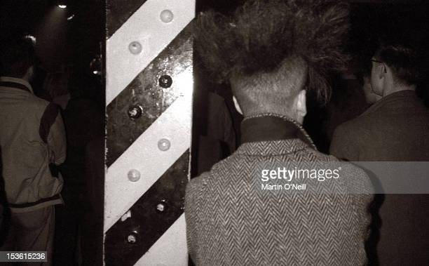 A music fan leans against one of the iconic yellow and black girders at the famous Hacienda Club Manchester circa 1981