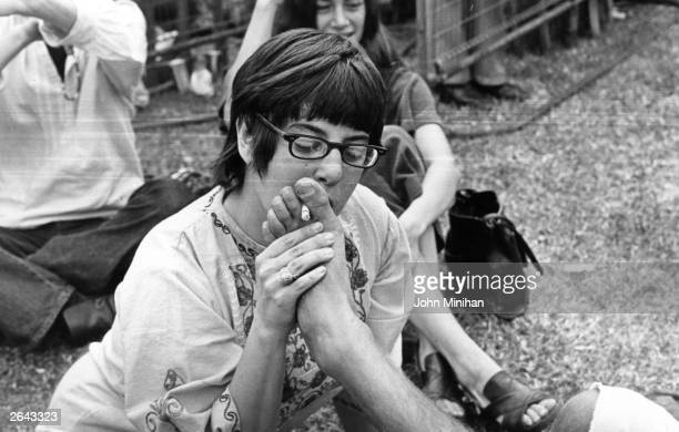 A music fan smokes a cigarette held in friend's toes at a rock concert in London's Hyde Park