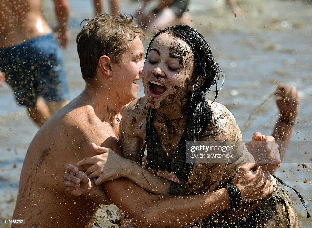 Music fans play in muddy water before the start of the 'Woodstock festival Poland' in Kostrzyn nad Odra on August 2, 2012. AFP PHOTO / JANEK SKARZYNSKI