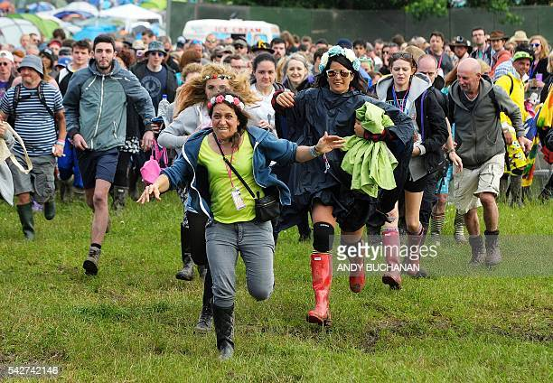 Music fans run to get to the front of the Pyramid Stage on day three of the Glastonbury Festival of Music and Performing Arts on Worthy Farm near the...