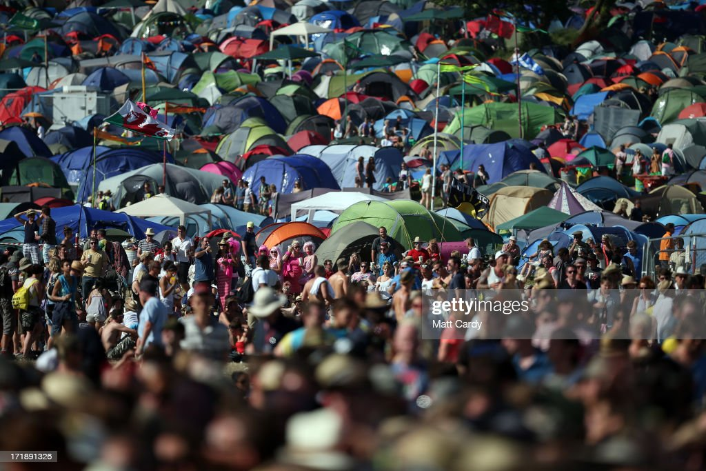 Music fans walk around the Pyramid Stage at the Glastonbury Festival of Contemporary Performing Arts site at Worthy Farm, Pilton on June 29, 2013 near Glastonbury, England. The wholesale market caters for traders throughout the Festival who are estimated to provide 3 million meals for festival goers, crew and performers. Gates opened on Wednesday at the Somerset diary farm that will be playing host to one of the largest music festivals in the world and this year features headline acts Artic Monkeys, Mumford and Sons and the Rolling Stones. Tickets to the event which is now in its 43rd year sold out in minutes and that was before any of the headline acts had been confirmed. The festival, which started in 1970 when several hundred hippies paid 1 GBP to watch Marc Bolan, now attracts more than 175,000 people over five days.