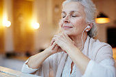 Mature woman with earphones listening to music