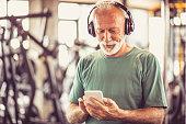 Senior man at gym listening music.