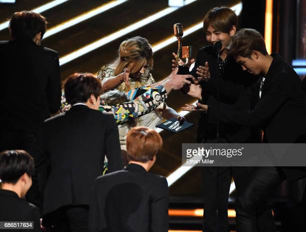 Music group BTS accepts the Top Social Artist award from recording artist Lindsey Stirling onstage during the 2017 Billboard Music Awards at TMobile...