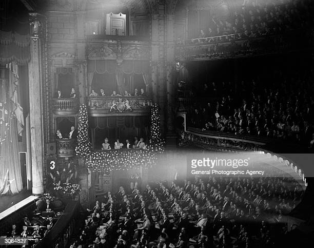 A music hall audience in a crowded theatre the boxes including the royal box are full and act No3 is on stage