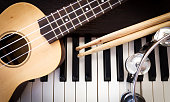 Music instruments. Ukulele, drum sticks, tambourine on piano. Top view with dark vignette.