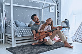 Young father teaching his little daughter to play guitar and smiling while sitting on the floor in bedroom