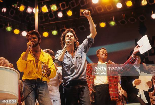 Live Aid George Michael of Wham Bob Geldof and Andrew Ridgeley performing on stage during the finale at Wembley Stadium London England 7/13/1985...