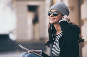 Side view of beautiful young woman in sunglasses adjusting her headphones and looking away with smile while sitting outdoors