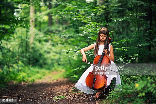 Music of nature - little cellist playing in beautiful forest