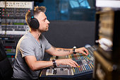 Serious deejay or music operator working in recording studio