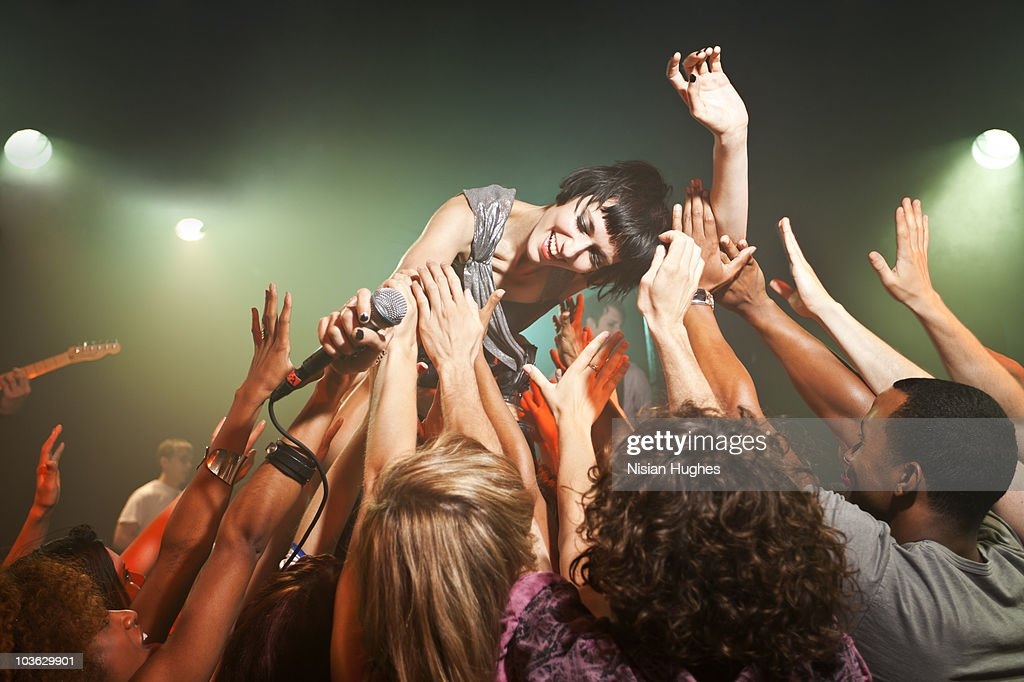 Music performer crowd surfing : Stock Photo