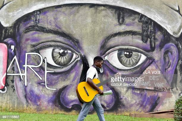 A music student of the National superior Institute of Arts and cultural action school in Abidjan walks with a guitar in front of a painting on a wall...
