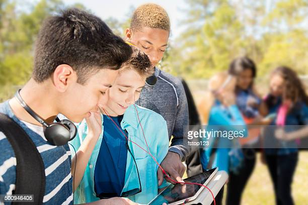 Music: Teenage friends listen to music on digital tablet.  Park.