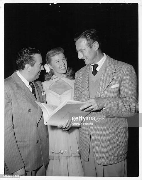 Musical director Ray Heindorf Doris Day and music synchronizer Sid Sidney discuss the score of one of her songs in between scenes from the film 'On...