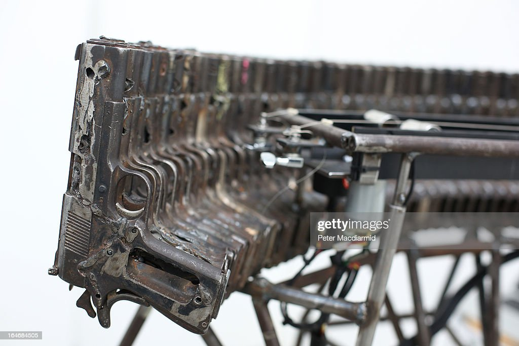 A musical instrument made from recycled gun parts is shown at Pedro Reyes' 'Disarm' exhibition at the Lisson Gallery on March 26, 2013 in London, England. Mexican artist Pedro Reyes received 6,700 destroyed weapons from the Mexican government from which he sculpted two groups of instruments. The first, a series titled Imagine, is an orchestra of fifty instruments, from flutes to string and percussion instruments, designed to be played live. The second, Disarm, is an installation of mechanical musical instruments, which can either be automated or played live by an individual operator using a laptop computer or midi keyboard.