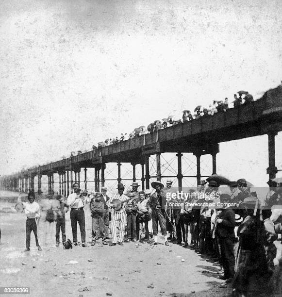 A musical troupe entertains the holidaymakers under Margate Pier circa 1860