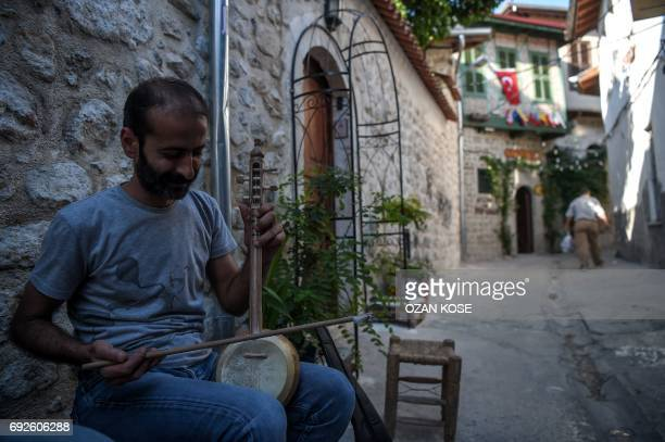 A musican plays a traditional 'kemani' at the historical streets of Antakya on June 5 2017 in Hatay / AFP PHOTO / OZAN KOSE