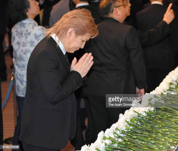 Musican Tetsuya Komuro offers a flower at an altar at the farewell meeting for late musician Hiroshi Kamayatsu on May 2 2017 in Tokyo Japan