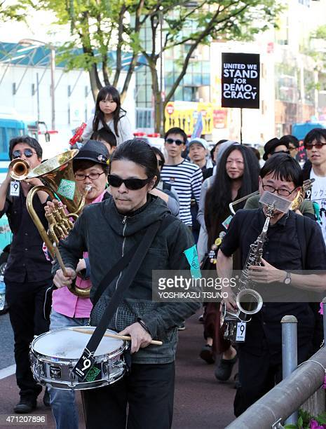 Musician activists march in protest against the construction of the new US military base in Okinawa during a rally in Tokyo on April 26 2015 Japanese...
