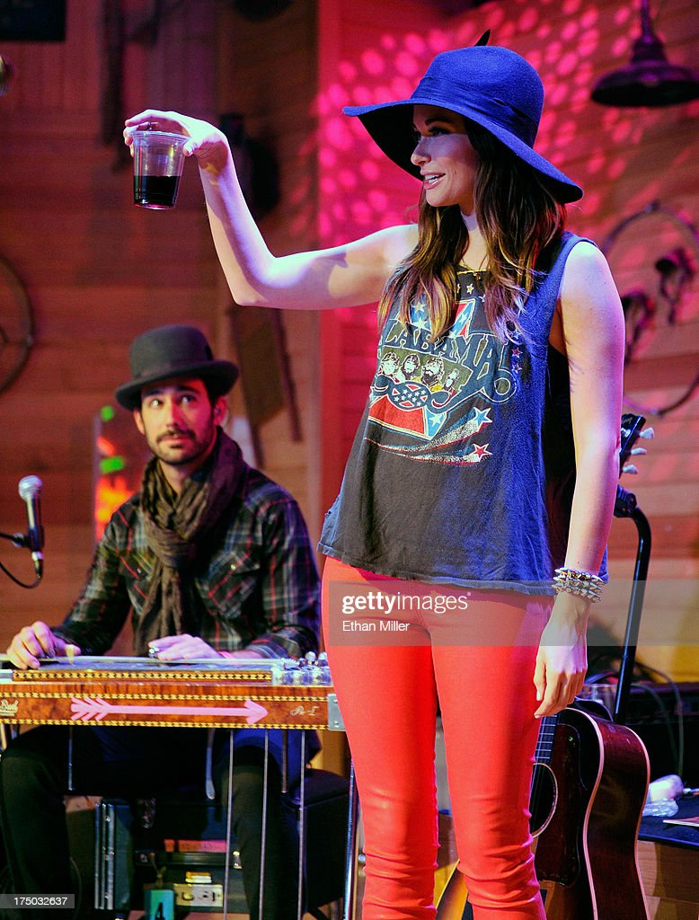 Musician Adam Ollendorff (L) looks on as singer/songwriter <a gi-track='captionPersonalityLinkClicked' href=/galleries/search?phrase=Kacey+Musgraves&family=editorial&specificpeople=4103138 ng-click='$event.stopPropagation()'>Kacey Musgraves</a> greets the crowd at Gilley's Saloon, Dance Hall & Bar-B-Que at the Treasure Island Hotel & Casino as she tours in support of the album 'Same Trailer Different Park' on July 29, 2013 in Las Vegas, Nevada.