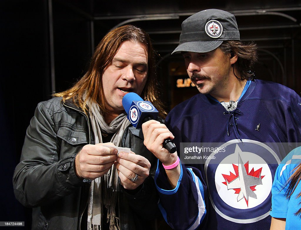 Musician <a gi-track='captionPersonalityLinkClicked' href=/galleries/search?phrase=Alan+Doyle+-+Musician&family=editorial&specificpeople=707870 ng-click='$event.stopPropagation()'>Alan Doyle</a> (left) of the group Great Big Sea announces the winning 50/50 number alongside Winnipeg Jets Game night host Dave Wheeler during a stoppage of play between the Winnipeg Jets and Montreal Canadiens at the MTS Centre on October 15, 2013 in Winnipeg, Manitoba, Canada.