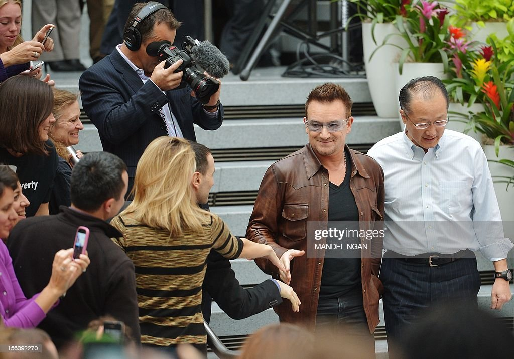 Musician and activist Bono (2nd R) and World Bank Group President Jim Yong Kim (R) arrive for a discussion on ending poverty November 14, 2012 in the atrium of the World Bank Headquarters in Washington, DC. AFP PHOTO/Mandel NGAN