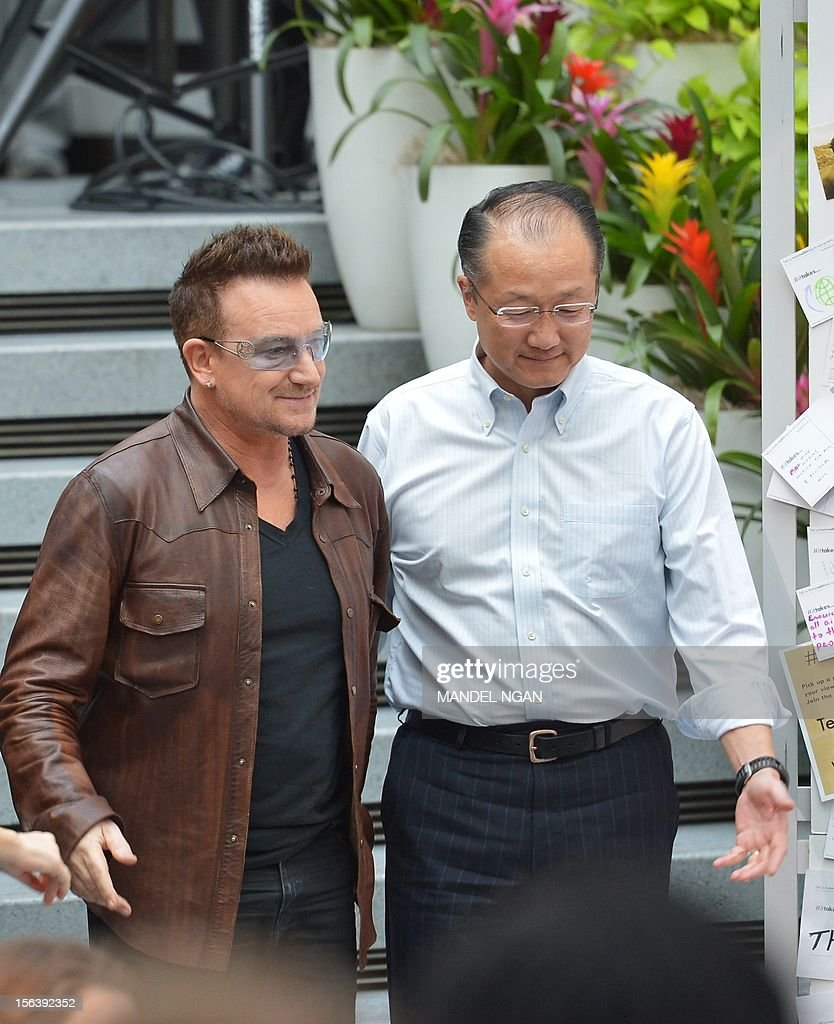 Musician and activist Bono (L) and World Bank Group President Jim Yong Kim arrive for a discussion on ending poverty November 14, 2012 in the atrium of the World Bank Headquarters in Washington, DC. AFP PHOTO/Mandel NGAN