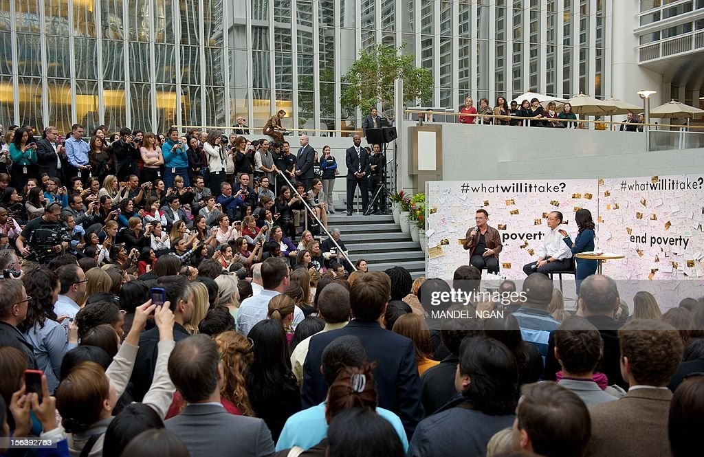 Musician and activist Bono (L) speaks as World Bank Group President Jim Yong Kim (2nd R) and moderator Isha Sesay (R) look on during a discussion on ending poverty November 14, 2012 in the atrium of the World Bank Headquarters in Washington, DC. AFP PHOTO/Mandel NGAN