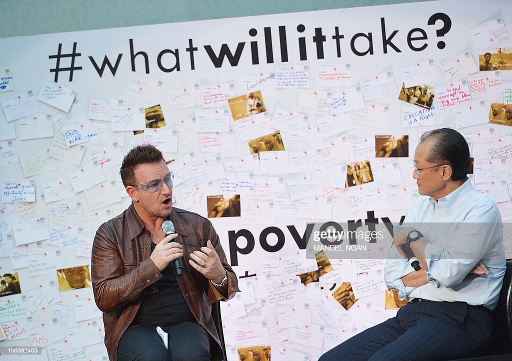 Musician and activist Bono (L) speaks during a discussion on ending poverty as World Bank Group President Jim Yong Kim watches November 14, 2012 in the atrium of the World Bank Headquarters in Washington, DC. AFP PHOTO/Mandel NGAN