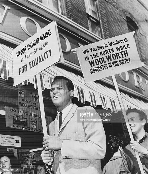 Musician and actor Harry Belafonte and protesters holding signs and marching during a protest against segregation by Woolworths department stores 1960