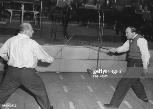 Musician and comic Gerard Hoffnung duels with pianist Joseph Cooper during rehearsals for Hoffnung's 'Interplanetary Music Festival' at the Royal...
