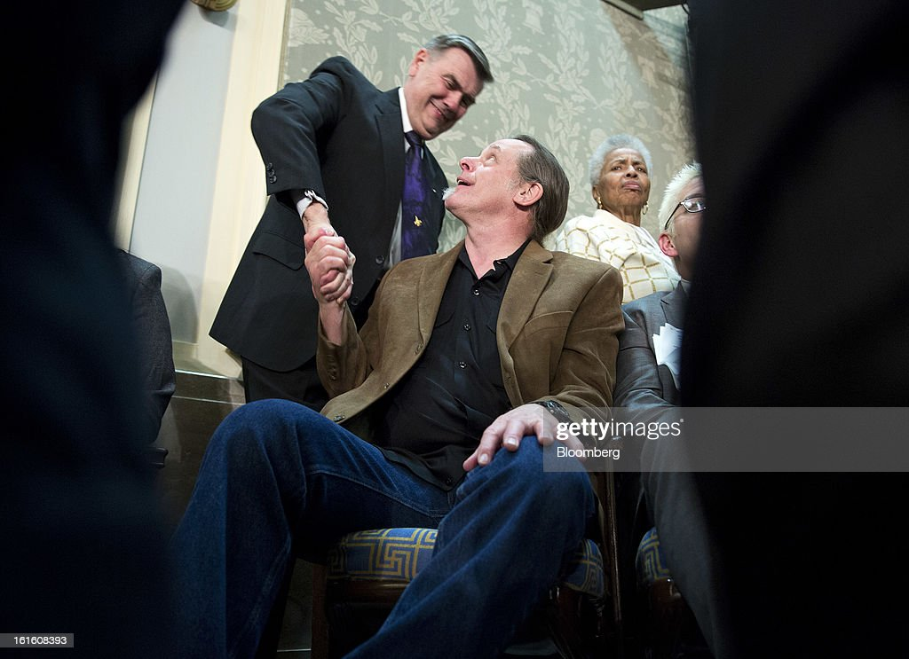 Musician and pro-gun activist <a gi-track='captionPersonalityLinkClicked' href=/galleries/search?phrase=Ted+Nugent&family=editorial&specificpeople=221432 ng-click='$event.stopPropagation()'>Ted Nugent</a>, seated, greets a guest before U.S. President Barack Obama's State of the Union address to a joint session of Congress at the Capitol in Washington, D.C., U.S., on Tuesday, Feb. 12, 2013. Obama called for raising the federal minimum wage to $9 an hour and warned he'll use executive powers to get his way on issues from climate change to manufacturing if Congress doesn't act, laying out an assertive second-term agenda sure to provoke Republicans. Photographer: Joshua Roberts/Bloomberg via Getty Images