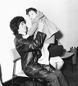 Musician Bill Wyman of the band 'The Rolling Stones' holding his son Stephen as they prepare to leave for America London Airport circa 1965