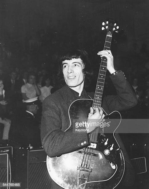 Musician Bill Wyman of the band 'The Rolling Stones' strumming his guitar at a concert circa 1965