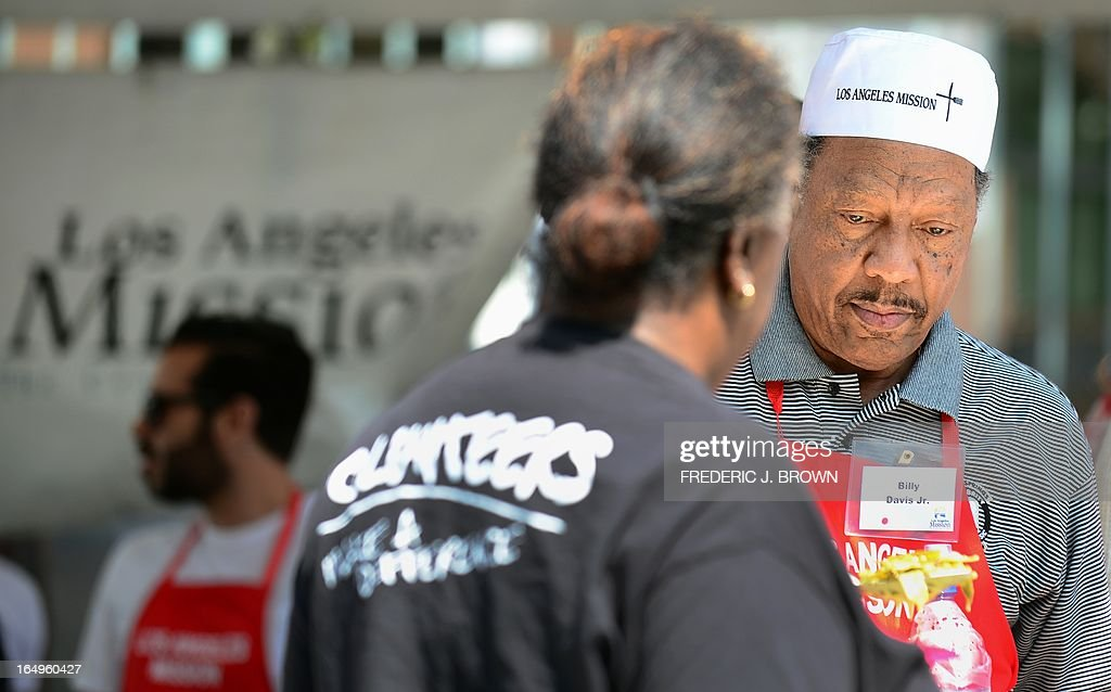 US musician Billy Davis Jr., seen here serving food, was one of many celebrities who volunteered to help out at the Los Angeles Mission's Good Friday event on Skid Row on March 29, 2013 in Los Angeles, California. Celebrities and volunteers joined together in giving something back to this community of the homeless, among the largest in the US, who were fed a fully-prepared meal and had the opportunity to be given foot washing and hygiene kits. Foot washing, a symbolic ritual of humbleness and respect derived from Jesus Christ's washing of his disciples feet at the Last Supper, was offered by the Los Angeles Health Center and volunteers. AFP PHOTO/Frederic J. BROWN