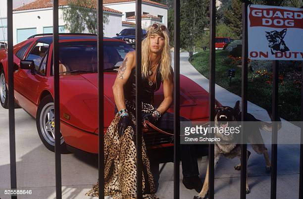 Musician Bret Michaels behind gate with guard dog