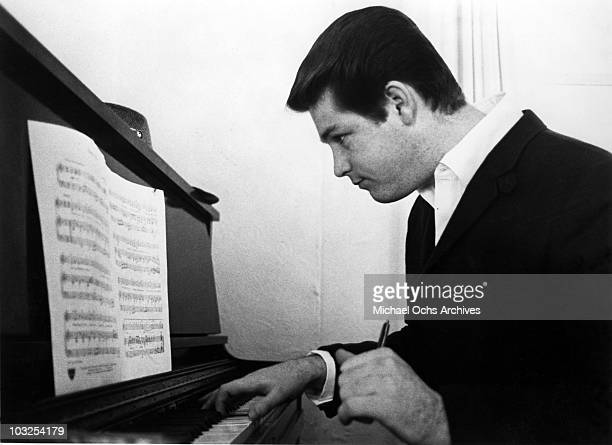 Musician Brian Wilson of the rock and roll band 'The Beach Boys' works on a composition on an upright piano while reading music in 1964 in Los...