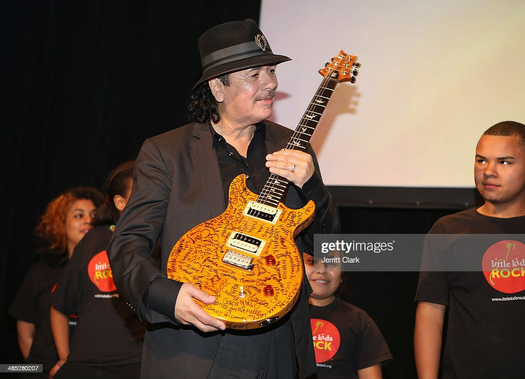 Musician Carlos Santana accepts a guitar signed by 300 students of the Little Kids Rock program funded by his Milagros Foundation during the HBO Latino NYC Premiere of 'Santana: De Corazon' at Hudson Theatre on April 16, 2014 in New York City.