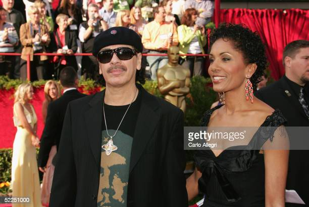 Musician Carlos Santana and his wife Deborah King Santana arrive at the 77th Annual Academy Awards at the Kodak Theater on February 27 2005 in...