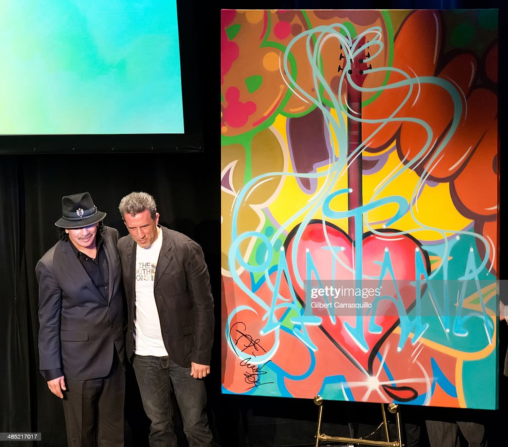 Musician Carlos Santana and iconic graffiti artist and muralist, John 'Crash' Matos on stage at the 'Santana De Corazon' screening at The Hudson Theatre on April 16, 2014 in New York City.