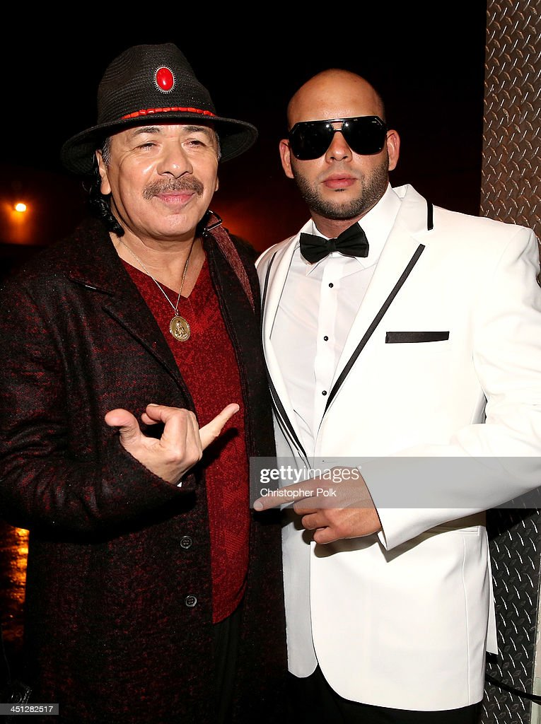 Musician Carlos Santana and singer Sessino pose backstage during the 14th Annual Latin GRAMMY Awards held at the Mandalay Bay Events Center on November 21, 2013 in Las Vegas, Nevada.