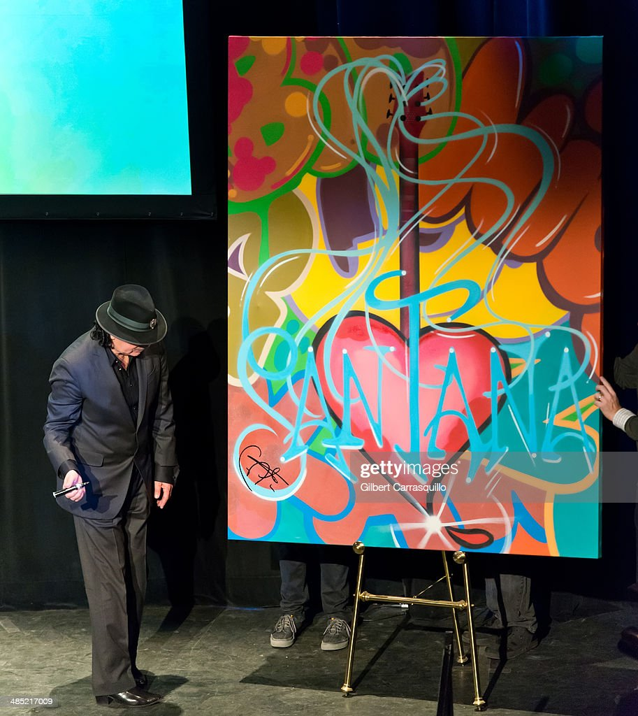 Musician Carlos Santana signs a graffiti paintig by iconic graffiti artist and muralist, John 'Crash' Matos on stage at the 'Santana De Corazon' screening at The Hudson Theatre on April 16, 2014 in New York City.