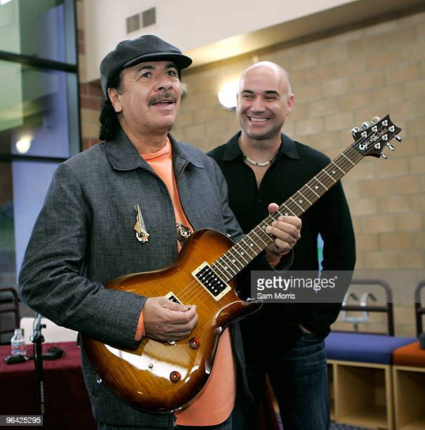 Musician Carlos Santana strums a guitar as former tennis player Andre Agassi looks on after touring the Andre Agassi College Preparatory Academy on...