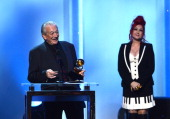Musician Charlie Musselwhite accepts the Best Blues Album award for 'Get Up' onstage from musician Cyndi Lauper during the 56th GRAMMY Awards...