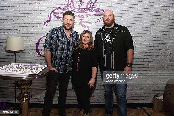 Musician Chris Young poses for a photo with winners of the #GiveACrown sweepstakes Jennifer Foster and Jarod Foster in the Crown Royal Lounge at...