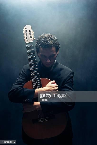 Musician cradling acoustic guitar