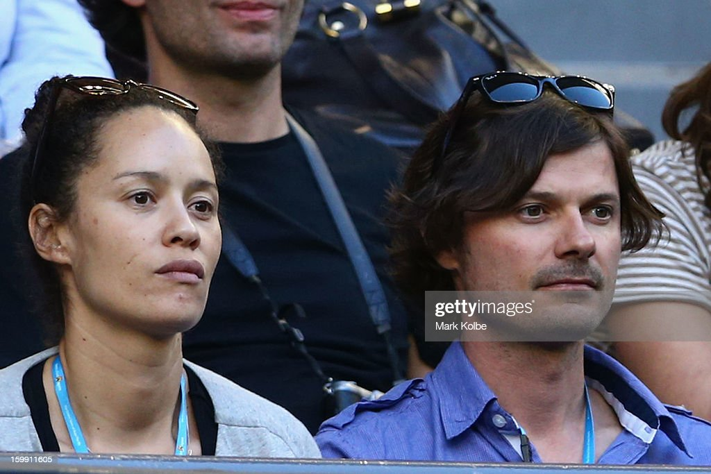 Musician Darren Middleton (R) watches Jo-Wilfred Tsonga of France and Roger Federer of Switzerland in their Quarterfinal match during day ten of the 2013 Australian Open at Melbourne Park on January 23, 2013 in Melbourne, Australia.