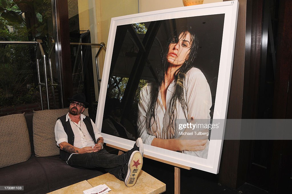 Musician Dave Stewart poses with one of his portraits of Demi Moore at the opening of his photography exhibition 'Dave Stewart: Jumpin' Jack Flash & The Suicide Blonde' at Morrison Hotel Gallery on July 12, 2013 in West Hollywood, California.
