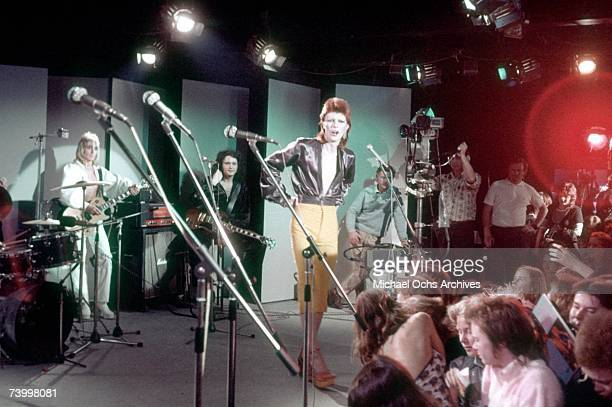 Musician David Bowie performs with his band including Mick Ronson on guitar in 1973